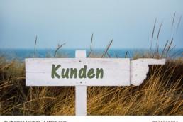 Wegweiser am Dünenstrand mit der Aufschrift Kunden